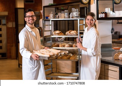 Portrait of two young bakers standing at bakery.