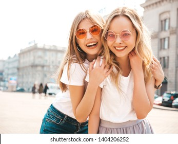 Portrait of two young beautiful blond smiling hipster girls in trendy summer white t-shirt clothes. Sexy carefree women posing on street background. Positive models having fun in sunglasses.Hugging