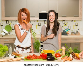 portrait of two young beautiful caucasian women standing in kitchen and laughing, one of them biting carrot