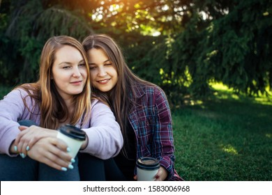 Portrait of two young beautiful girls sitting next to each other on the green lawn in the Park, copy space. Female lesbian couple enjoys intercourse outdoors. LGBT community concept.