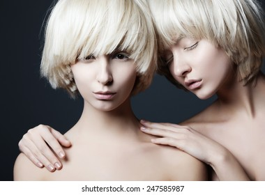 Portrait of two young beautiful girls twins in the studio