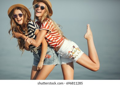 Portrait of two young beautiful girls in trendy stripe shirt, beach hat, sunglasses an jeans shirt on the sea. two friends having fun at the sea with cocktails on their hands.