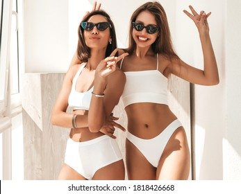 Portrait of two young beautiful smiling women in white lingerie. Sexy carefree models posing at balcony in the early morning. They hugging and going crazy in sunglasses. Show peace sign