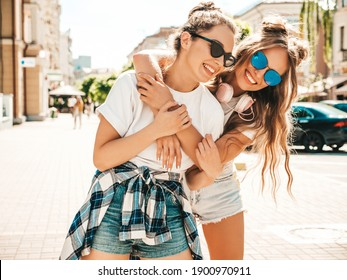 Portrait of two young beautiful smiling hipster female in trendy summer white t-shirt clothes.Sexy carefree women posing on street background. Positive models having fun, hugging and going crazy - Shutterstock ID 1900970911