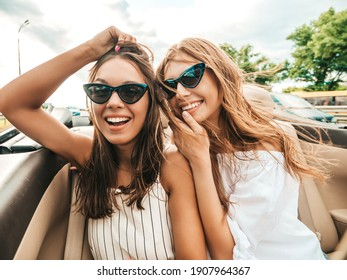 Portrait of two young beautiful and smiling hipster female in convertible car. Sexy carefree women driving cabriolet. Positive models riding and having fun in sunglasses