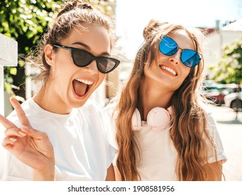 Portrait of two young beautiful smiling hipster female in trendy summer white t-shirt clothes.Sexy carefree women posing on street background. Positive models having fun, hugging and going crazy - Shutterstock ID 1908581956