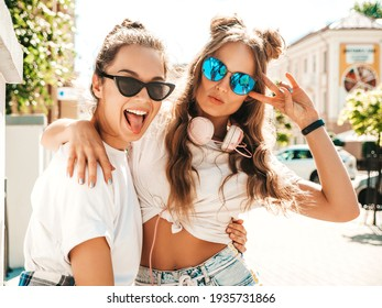 Portrait of two young beautiful smiling hipster female in trendy summer white t-shirt clothes.Sexy carefree women posing on street background. Positive models having fun, hugging and going crazy - Shutterstock ID 1935731866