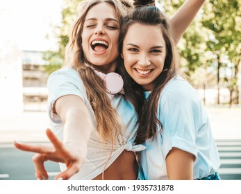 Portrait of two young beautiful smiling hipster female in trendy summer white t-shirt clothes.Sexy carefree women posing on street background. Positive models having fun, hugging and going crazy - Shutterstock ID 1935731878