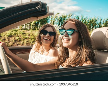 Portrait of two young beautiful and smiling hipster female in convertible car. Sexy carefree women driving cabriolet. Positive models riding and having fun in sunglasses outdoors.Enjoying summer days