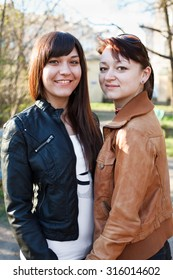 Portrait of two young beautiful women a girlfriend. Standing together. Looking at camera and smiling