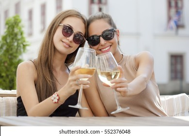Portrait of two young beautiful women having some wine.