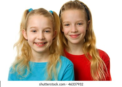 portrait of two young blonde girls looking in camera over white background