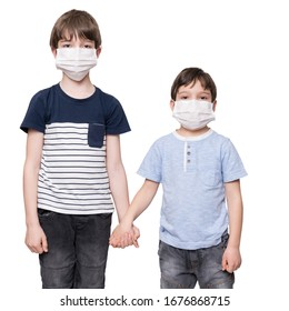 Portrait of two young boys wearing protective mask against the coronavirus holding hands, isolated on white background