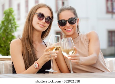 Portrait of two young brunettes having summer wine fun.