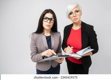 Portrait of two young buisness ladies in costumes isolated on background