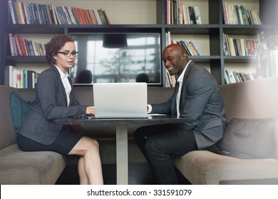 Portrait of two young business colleagues sitting at coffee shop working together on laptop. Diverse business team working at cafe.