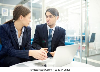Portrait of two young business people talking in office while collaborating on startup project, copy space
