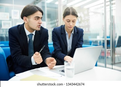 Portrait of two young business people using laptop in office while collaborating on startup project, copy space