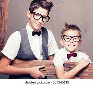 Portrait of two young elegant brothers holding wooden frame, looking at camera, wearing fashionable eyeglasses and bow tie.