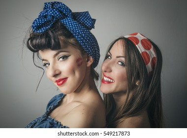 Portrait of two young female friends in retro clothing with hair bands looking over shoulder