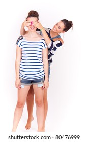 portrait of two young female friends playing who is and having fun on white background