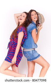 portrait of two young female friends playing and having fun on white background