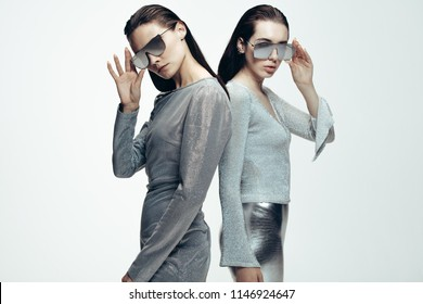 Portrait of two young females in silver outfit and mirrored sunglasses looking at camera. Female models in futuristic look standing on grey background.