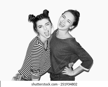 Portrait of two young girl having fun and laughing. One hugging other. Top knot hairdo. White background, not isolated. Inside