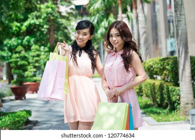 Portrait of two young girlfriends with shopping bags