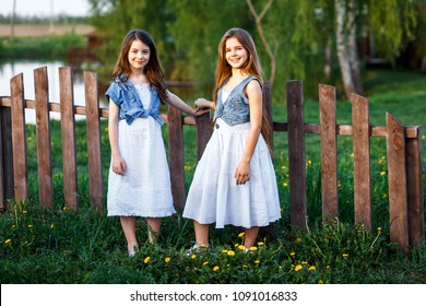 A portrait of two young girls with blue eyes in white dresses and jeans wests  in the garden near the fence enjoying, chattering and having fun ath the subset