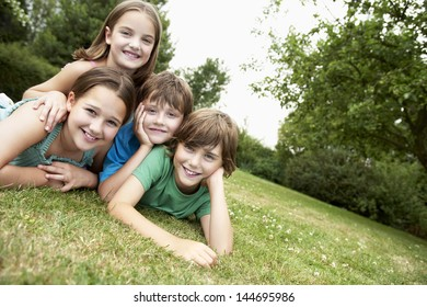 Portrait of two young girls and boys lying in park together