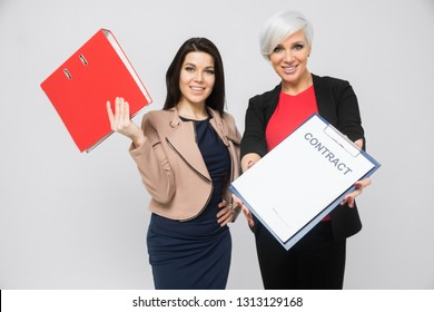 Portrait of two young girls with a folder and a contract in their hands isolated on a light background