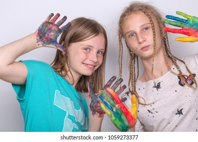 Portrait two young girls and hands painted in colorful paints, close up