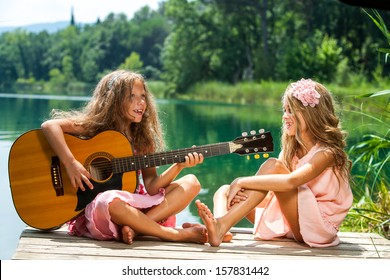 Portrait of two young girls singing together at lakeside.
