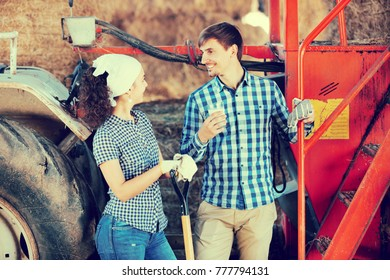 Portrait of two young happy farmers taking a pause and holding the glass with milk