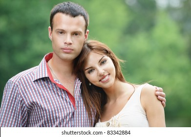Portrait of two young happy lovers at summer green park.