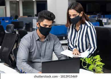 Portrait of two young Indian businesspeople wearing Covid protection masks while discussing project at workstation, corporate environment.