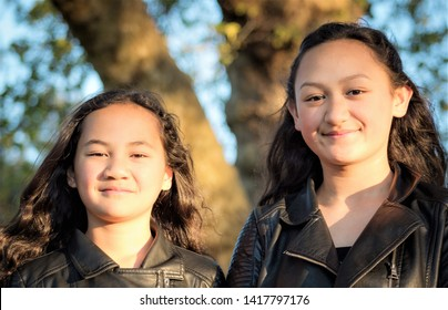 Portrait of two young Maori sisters taken outdoors in a park.