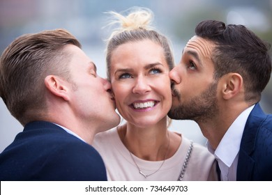 portrait of two young men kissing blond woman on her cheeks