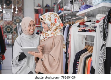 Portrait of a two young muslim business team with beautiful smile holding digital tablet while standing in their fashion boutique, female owner