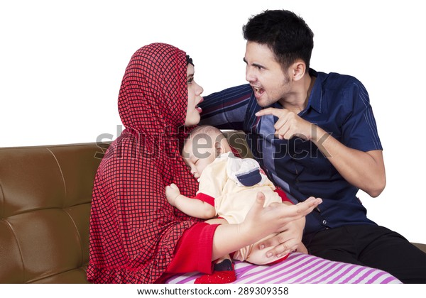 Portrait of two young parents having fight while holding a baby boy, isolated on white