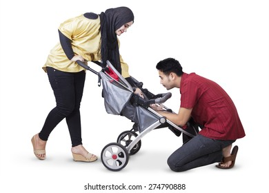 Portrait of two young parents take care their baby in the baby carriage, isolated on white background