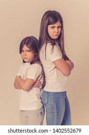 Portrait of two young siblings standing back to back not talking to each other after having an argument. Sisters not interacting angry and mad one to another in bad relationship. Studio shot.