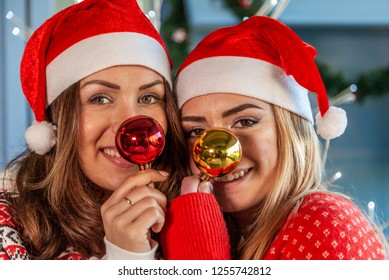 portrait of two young sister having fun making funny faces with Christmas balls