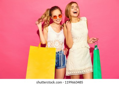 Portrait of two young stylish smiling blond women holding shopping bags. Girls dressed in summer hipster clothes. Positive models posing over pink blackground