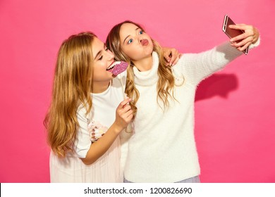 Portrait of two young stylish smiling blond women. Girls dressed in summer hipster clothes. Positive models making selfie on smartphone on pink background