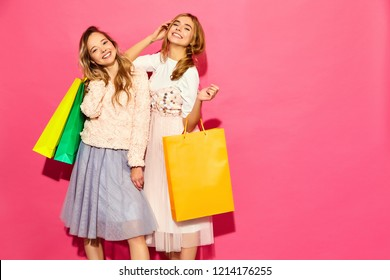 Portrait of two young stylish smiling blond women holding shopping bags. Girls dressed in summer hipster clothes. Positive models posing over pink background