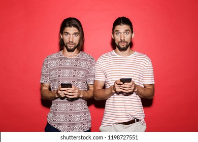 Portrait of a two young surprised twin brothers isolated over red background, using mobile phones
