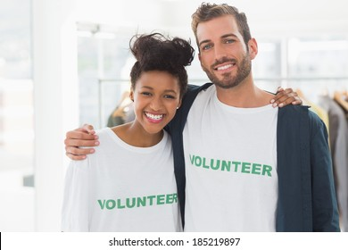 Portrait of two young volunteers with arms around standing indoors