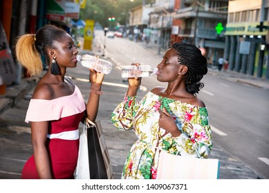 portrait of two young women carrying bags and drinking together drinking water.